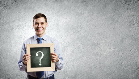 Young smiling businessman holding chalkboard with question sign Stock Photo