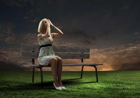 eyes closing: Mujer joven sentada en el banco de cerrar los ojos con las palmas