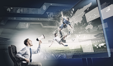 Young man screaming in megaphone and watching football match photo