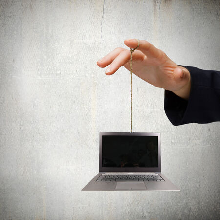 determinism: Close up of business person hand holding laptop on rope