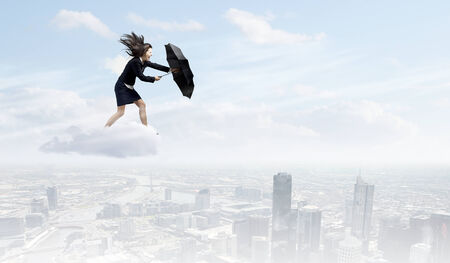 late 20s: Young determined businesswoman walking against strong wind Stock Photo