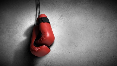 knockout: Pair of red boxing gloves hanging on wall