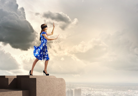 disoriented: Young woman in blue dress standing on roof edge