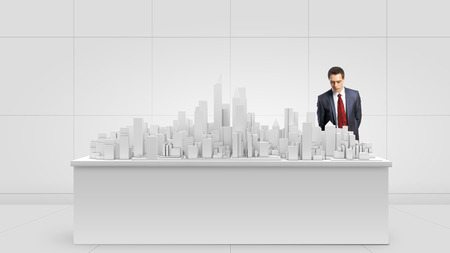 construction project: Young businessman examining model of construction project Stock Photo