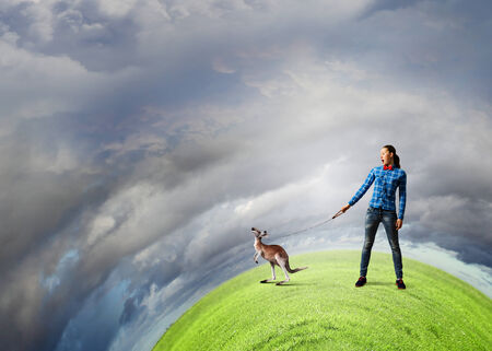 positivism: Young woman in casual holding kangaroo on lead Stock Photo