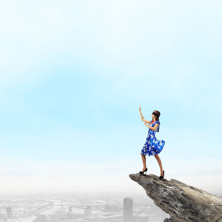 disoriented: Young woman in blue dress standing on mountain edge