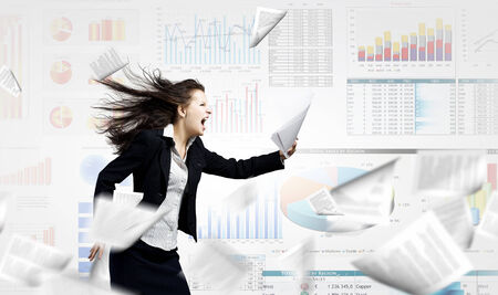 woman screaming: Young determined businesswoman walking against strong wind Stock Photo
