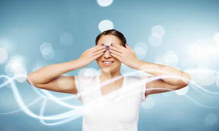 eyes closing: Mujer joven en blanco camisa cierre los ojos con las palmas Foto de archivo