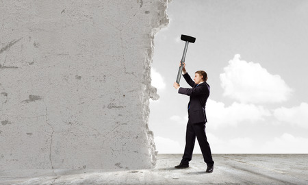 determinism: Young determined businessman crashing wall with hammer