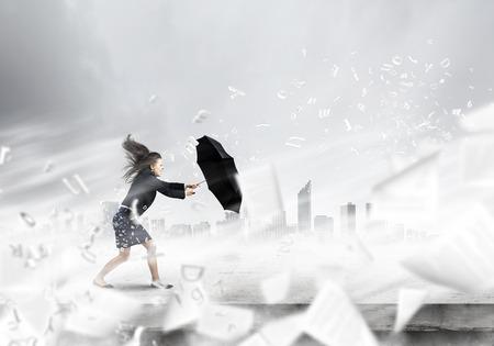 若い実業家が強い風に逆らって歩く決定
