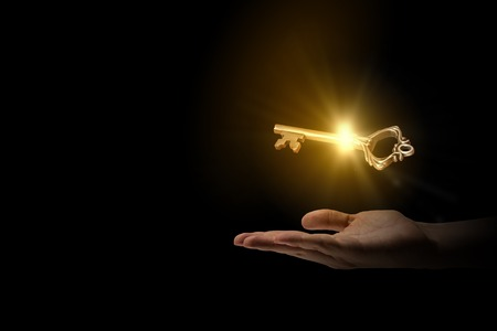 business success: Close up of human hand holding golden key