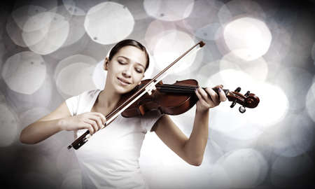 Portrait of young pretty woman playing violin photo