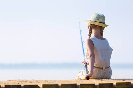 Girl in a dress and a hat with a fishing rod fishing from the pier photo