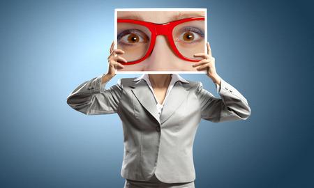 eyes closeup: Unrecognizable businesswoman holding big photo with eyes Stock Photo