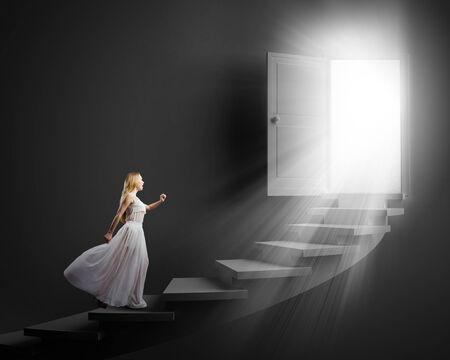 Jonge vrouw in witte lange jurk intensivering van de trap