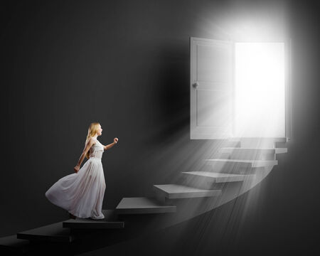 Young woman in white long dress stepping up the staircase Фото со стока