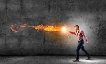 Young man in casual throwing magic fire balls photo