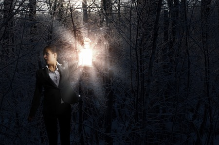way out: Young pretty businesswoman with lantern in darkness