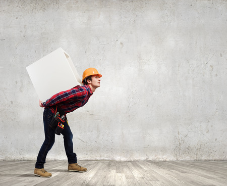 Young builder man in hardhat carrying white blank cube on back