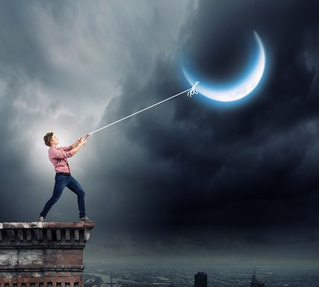 Young man in casual catching moon with rope photo