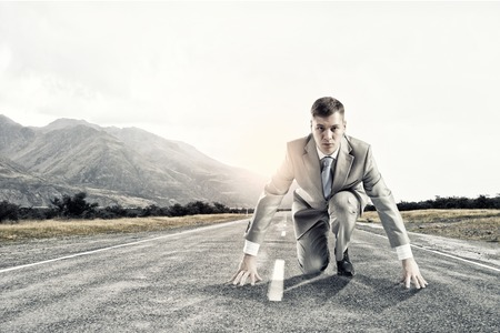 Young businessman standing in start pose ready to run photo