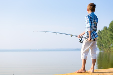 Boy in blue shirt standing on a pier with a fishing rod by the sea photo