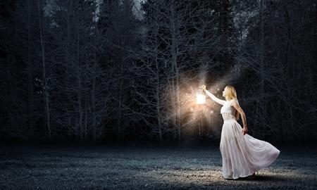 lampara magica: Mujer joven con la linterna para caminar en el bosque oscuro