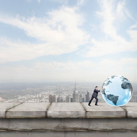 Young businessman rolling Earth planet up th hill photo