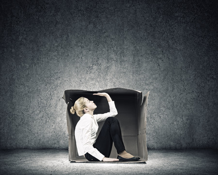 Young businesswoman trapped in carton box photo