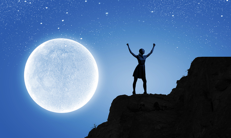 Silhouette of woman against full moon with hands up photo