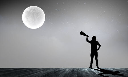 Silhouette of man at night screaming in megaphone photo
