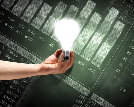 energy saving: Cierre plano de la mano que sostiene la bombilla con bocetos en el fondo Foto de archivo