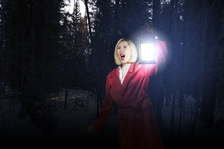 Young blonde in red cloak with lantern in night forest photo