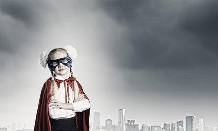 Cute girl of school age in superhero costume