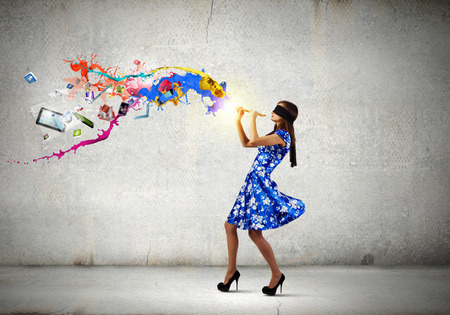 disoriented: Young woman in blue dress wearing blindfold playing fife Stock Photo