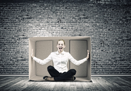 Young emotional woman trapped in carton box photo