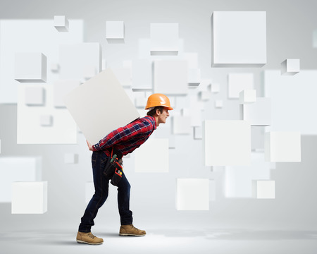 Young builder man in hardhat carrying white blank cube on back photo