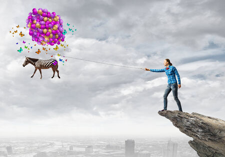 positivism: Young girl in casual with bunch of colorful balloons Stock Photo