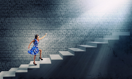 sense of security: Young woman in blue dress walking on ladder