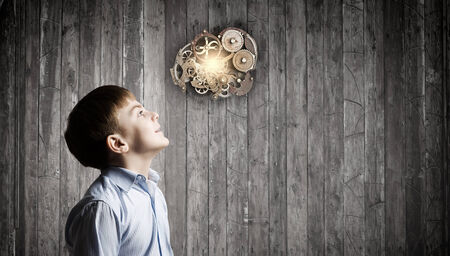 creative thinking: Cute boy of school age looking up at gears mechanism Stock Photo