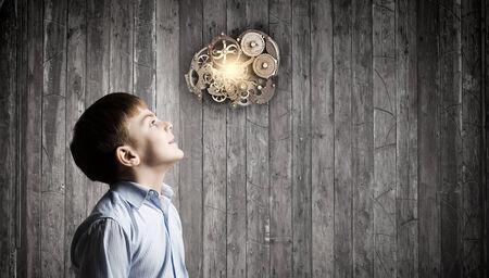 pensamiento creativo: El muchacho lindo de la edad escolar mirando al mecanismo de engranajes