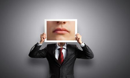 unrecognizable: Unrecognizable businessman hiding face behind photo of mouth
