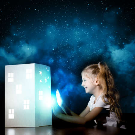 Little cute girl in darkness dreaming about home and family photo
