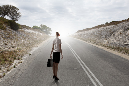 Rear view of businesswoman standing on road photo