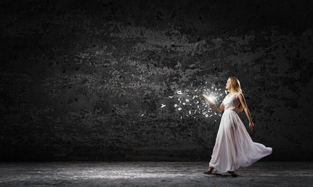 uneducated: Young woman in white long dress with book in hand