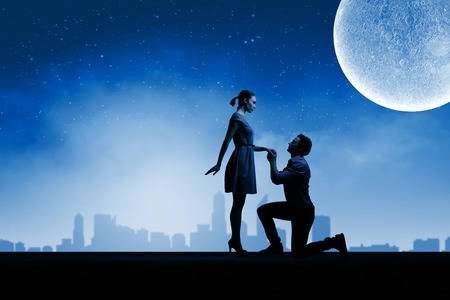 Silhouettes of romantic couple under the moon light photo