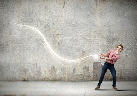 supernatural power: Young guy in casual pulling loop of light