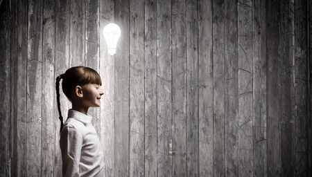 Cute girl of school age and electrical bulb above head