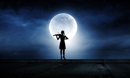 Silhouette of woman playing violin at night photo