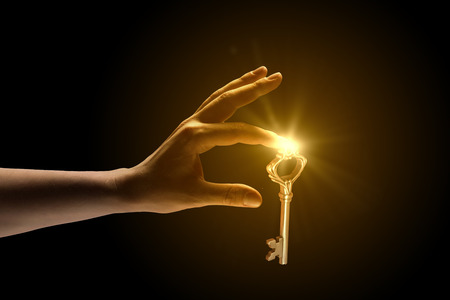 Close up of human hand catching golden key Stock Photo